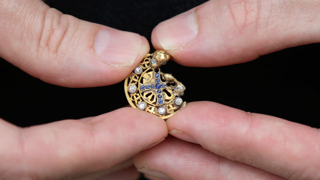 PHOTO: Mark Rubinstein holds a gold pendant with sapphires forming a cross inside a circle of diamonds, that he found while python hunting in the Florida Everglades, May 31, 2013.