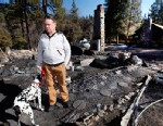 PHOTO: Rick Heltebrake looks over the burned-out cabin where Christopher Dorners remains were found after a police standoff near Big Bear, Calif., Feb. 15, 2013. Heltebrake is trying to claim the $1.2 million reward for Dorners capture.