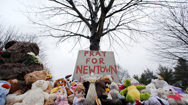 PHOTO: Stuffed animals and a sign calling for prayer rest at the base of a tree near the Newtown Village Cemetery in Newtown, Conn., Dec. 17, 2012.