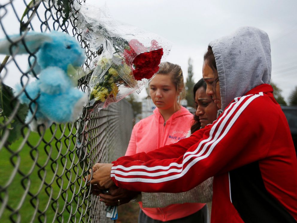 PHOTO: Student Tyanna Davis, right, places flowers on the fence bordering Marysville-Pilchuck High School in Marysville, Wash., Oct. 25, 2014.