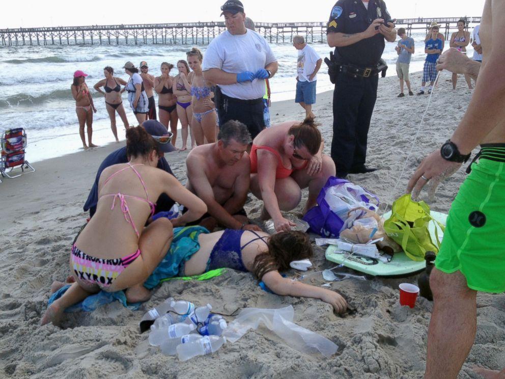PHOTO: Emergency responders assist a teenage girl at the scene of a shark attack in Oak Island, N.C., Sunday, June 14, 2015.