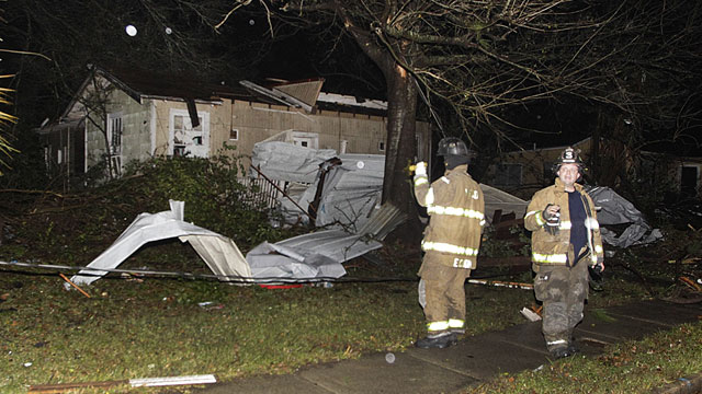 PHOTO: Firefighters go door-to-door on North Carlen Street in the Midtown section of Mobile, Ala. after a tornado touched down Tuesday, Dec. 25, 2012.