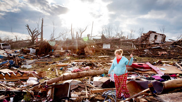 PHOTO: A resident of Henryville, Ind. looks through the debris on March 4, 2012, after a tornado destroyed her home.