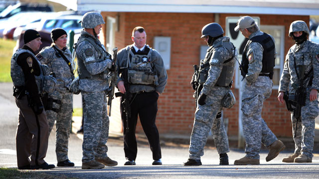 PHOTO: Local S.W.A.T. team members congregate near a parking lot on the campus of Virginia Tech to look for an armed man who suspected of killing a police officer on Dec. 8, 2011, in Blacksburg, Va.