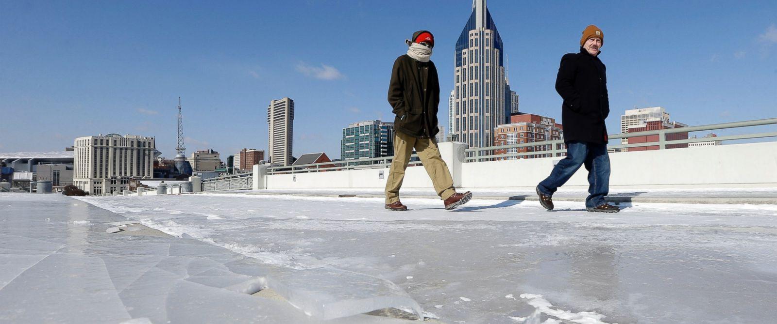 PHOTO: Austin Carlson, left, and Jim Post, of Jamestown, New York, walk across an ice-covered bridge on Feb. 19, 2015, in Nashville, Tenn.