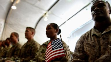 PHOTO: A U.S. soldier holds an American flag as he and others attend a naturalization ceremony at the U.S. base in Bagram, Afghanistan on July 4, 2013.