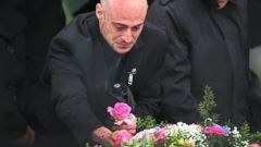 PHOTO: Joseph Amoroso, Bella Bonds biological father, wept as he took a pink rose from her coffin on Nov. 28, 2015, in Winthrop, Mass.