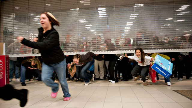PHOTO: Black Friday shoppers duck under the opening door of a Sears store at Great Lakes Mall in Mentor, Ohio, U.S., Nov. 25, 2011.