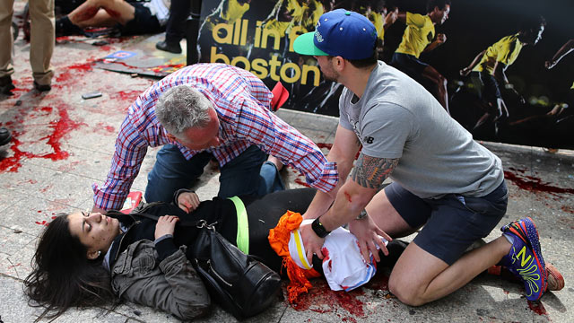 PHOTO: Bystanders help an injured woman at the scene of the first explosion on Boylston Street near the finish line of the 117th Boston Marathon.