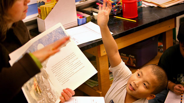 PHOTO: Third grade student Kao Xiong sits beside ELL teacher Concha Fernandez del Ray, during a reading lesson.