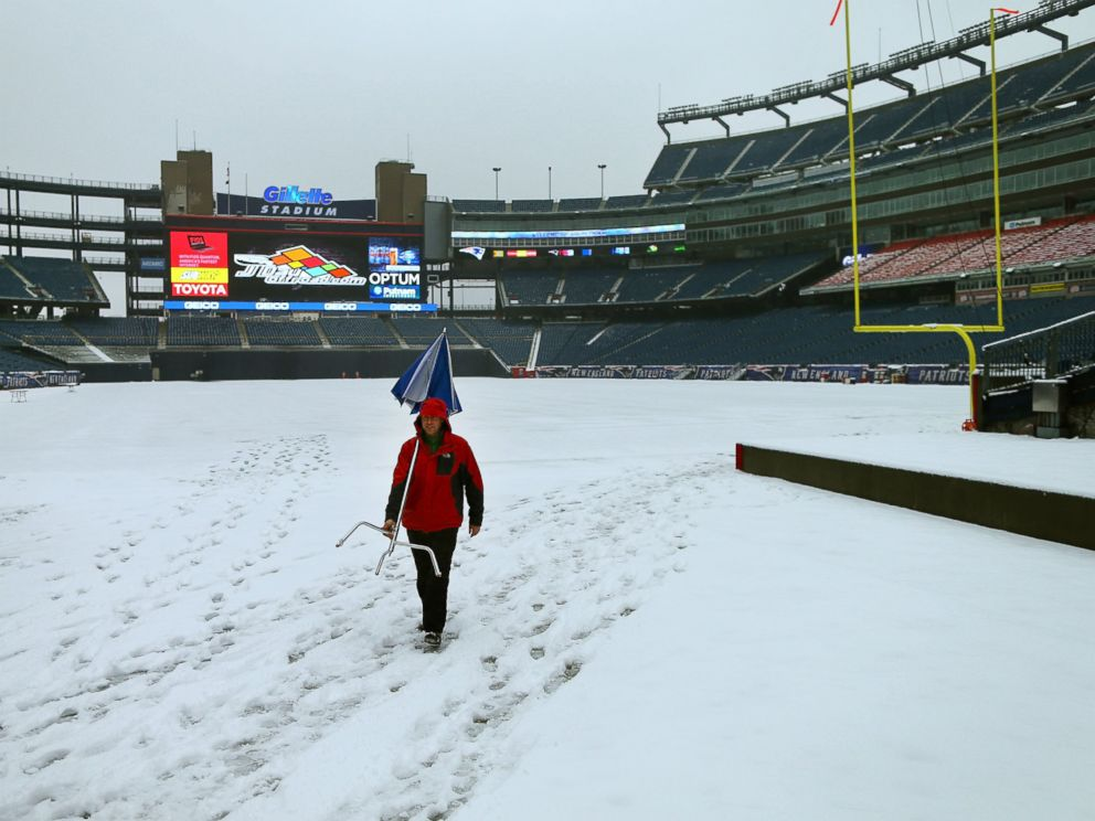 PHOTO: Snow covers the field at Gillette Stadium as a tv crew member walks by with an umbrella and stand, on Jan. 24, 2015.