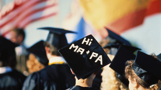 PHOTO: This stock photo of a high school graduation ceremony shows girl with message on mortarboard to her parents.