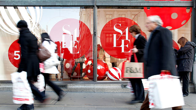 PHOTO: Pedestrians walk past a store window advertising Christmas sales discounts in London, U.K., Dec. 12, 2011.