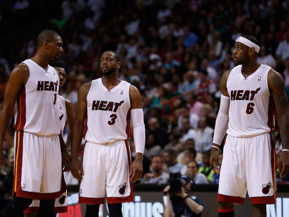 PHOTO: Chris Bosh, Dwyane Wade, and LeBron James of the Miami Heat look on during a game against the Houston Rockets at American Airlines Arena on March 16, 2014 in Miami.