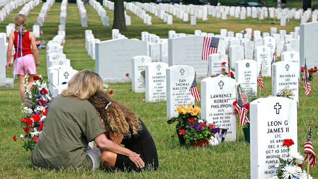 PHOTO: Crystal Lewis (L) and her daughter Morgan Lewis sit at the gravesite of Morgan's high school sweetheart, U.S. Marine Nicholas Cain Kirven, who was killed in Afghanistan in 2005, on Memorial Day at section 60 at Arlington National Cemetery May 28, 2