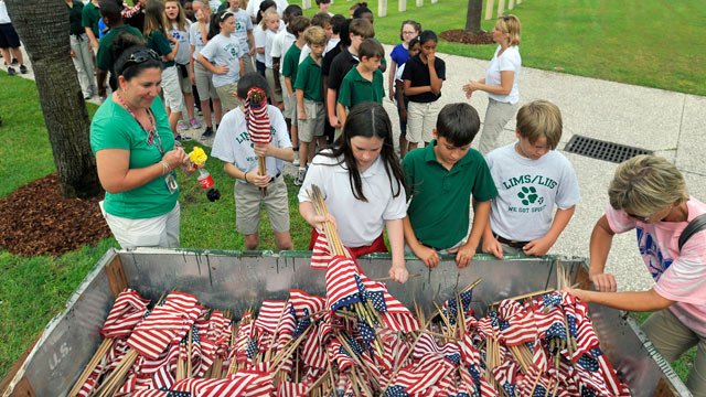 PHOTO: Teachers at Lady's Island Intermediate School hand out American flags to a group of fifth grade students at the Beaufort National Cemetery May 27, 2011 in Beaufort, South Carolina.