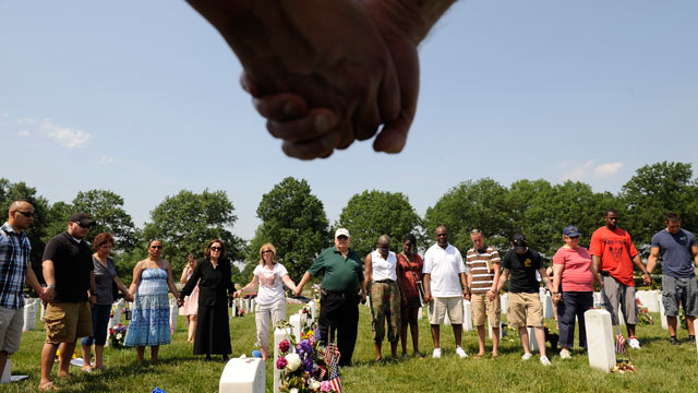 PHOTO: People hold hands during a moment of silence at Arlington National Cemetery on Memorial Day, May 30, 2011 in Arlington, VA.