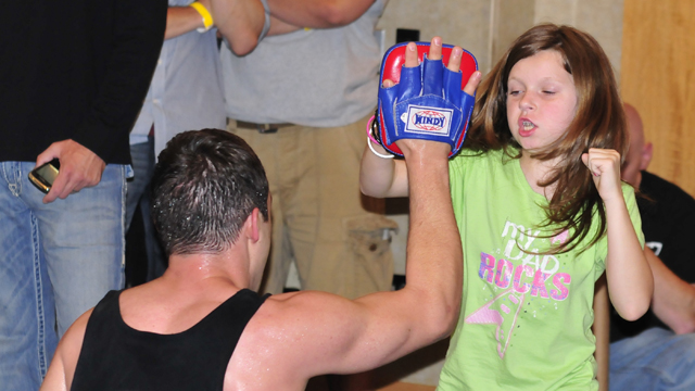 PHOTO: A young girl punches the hand of a MMA trainer during an open workout at the Hyatt Regency on June 24, 2011 in Pittsburgh, Penn.