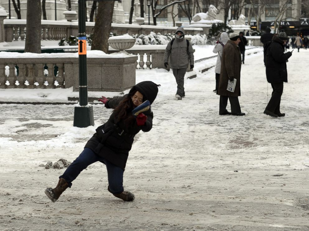 PHOTO: A woman falls on the ice and snow along 5th Avenue on Jan. 22, 2014 in New York.