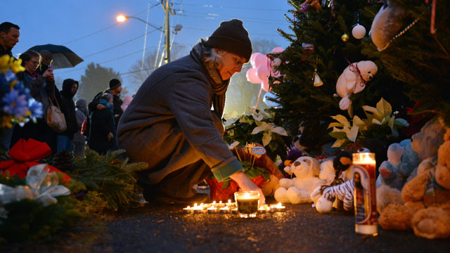 PHOTO: Tracy Kirk re-lights candles at a memorial near the Newtown Firehouse, Dec. 16, 2012, in Newtown, Conn.