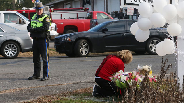 PHOTO: A police officer keeps watch as a woman kneels at a makeshift memorial outside a firehouse which was used as a staging area for families following the mass shooting at Sandy Hook Elementary School on December 15, 2012 in Newtown, Connecticut.