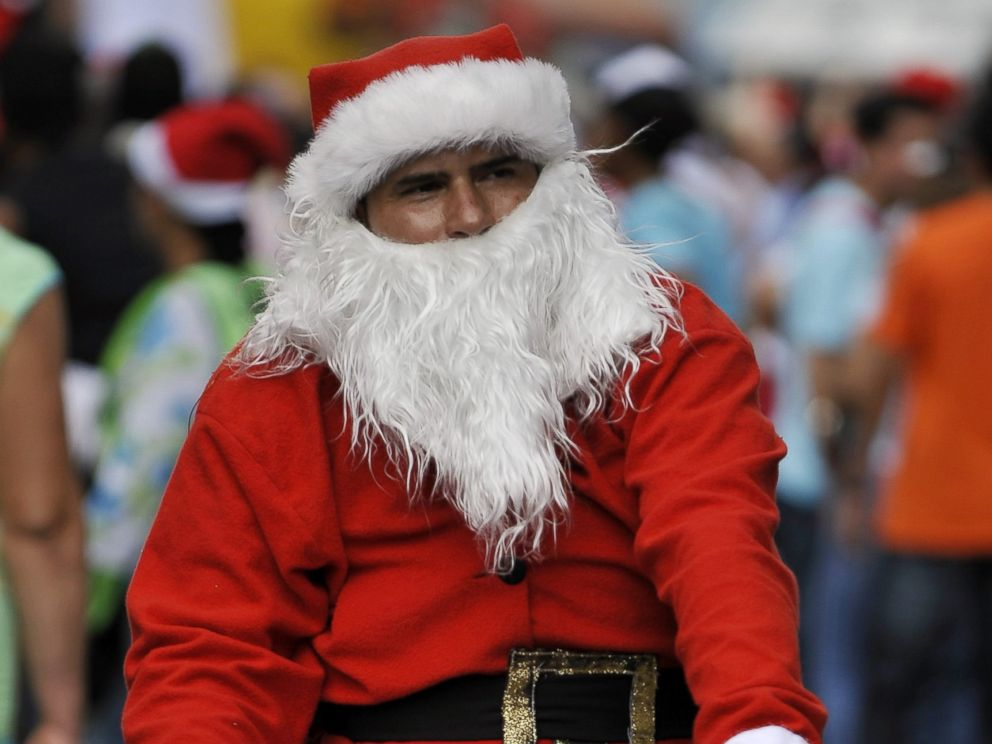 PHOTO: A man dressed as Santa Claus rides his bicycle with other hundreds along the streets of Cali, Colombia, on December 12, 2010 in a failed attempt to break the previous Guinness record of 12,000 people riding bikes dressed as Santa Claus.