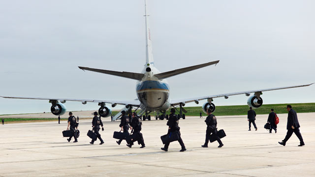 PHOTO: Members of the Secret Service and other staff walk behind Air Force One at Buckley Air Force Base, April 25, 2012 in Colorado.