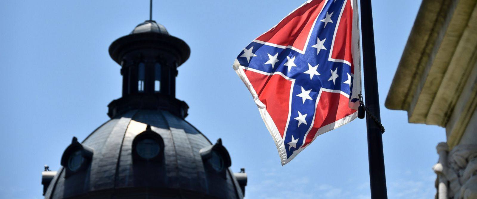 PHOTO: The South Carolina and American flags flying at half-staff behind the Confederate flag erected in front of the State Congress building in Columbia, South Carolina on June 19, 2015.
