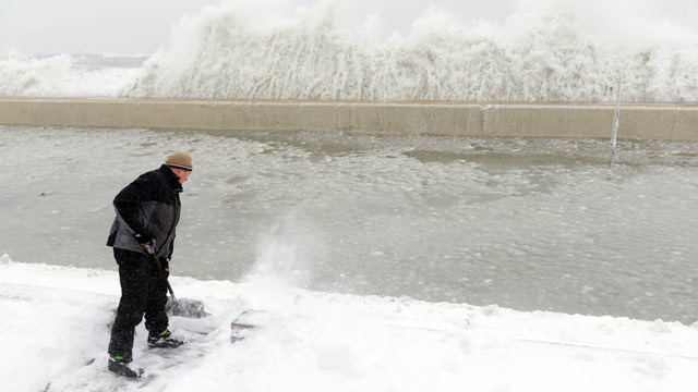 PHOTO: Mike Streeter shovels snow in his front yard as ocean water crashes over the sea wall just feet away on February 9, 2013 in Winthrop, Mass.