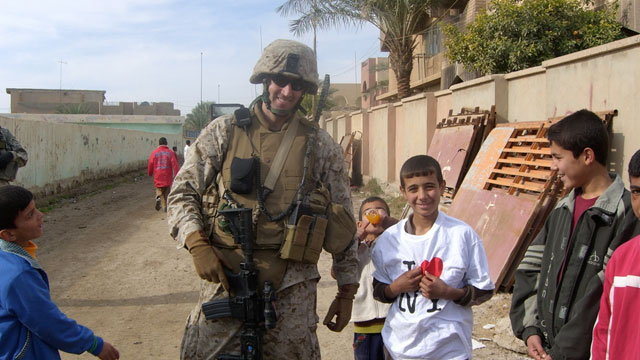 PHOTO: Owen West, Managing Director at Goldman Sachs poses with a young boy in Khalidiya, Iraq. Goldman Sachs Commodities team sponsored West?s Iraqi battalion, raising money as individuals, and donating goods. West said the ?I heart New York? T-shirt was