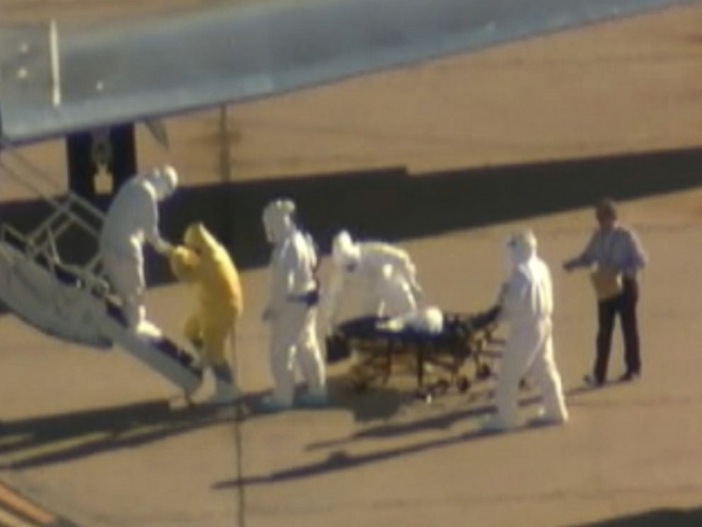PHOTO: A man without a hazmat suit assists in the transportation of Ebola patient Amber Vinson from an ambulance to a plane at the Dallas airport on Oct 15, 2014.