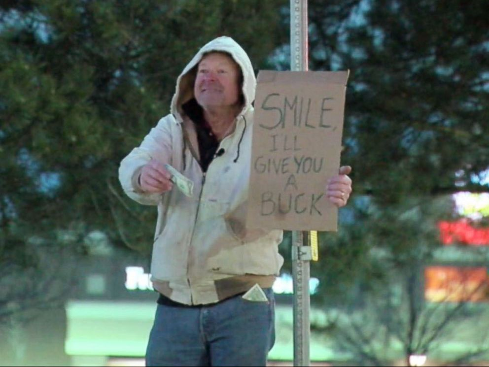 PHOTO: A man in Parker, Colo., gives out dollars for smiles on Dec. 28, 2015 in memory of Carl Ramsey, a high school friend of his who passed away at age 18.