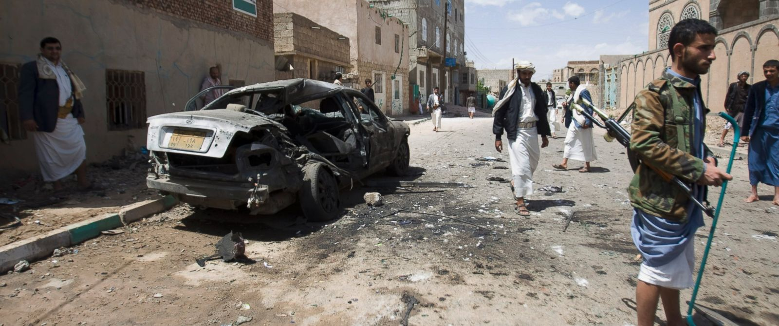 PHOTO: Shiite rebels, known as Houthis, stand near a damaged car after a bomb attack in Sanaa, Yemen, Friday, March 20, 2015.
