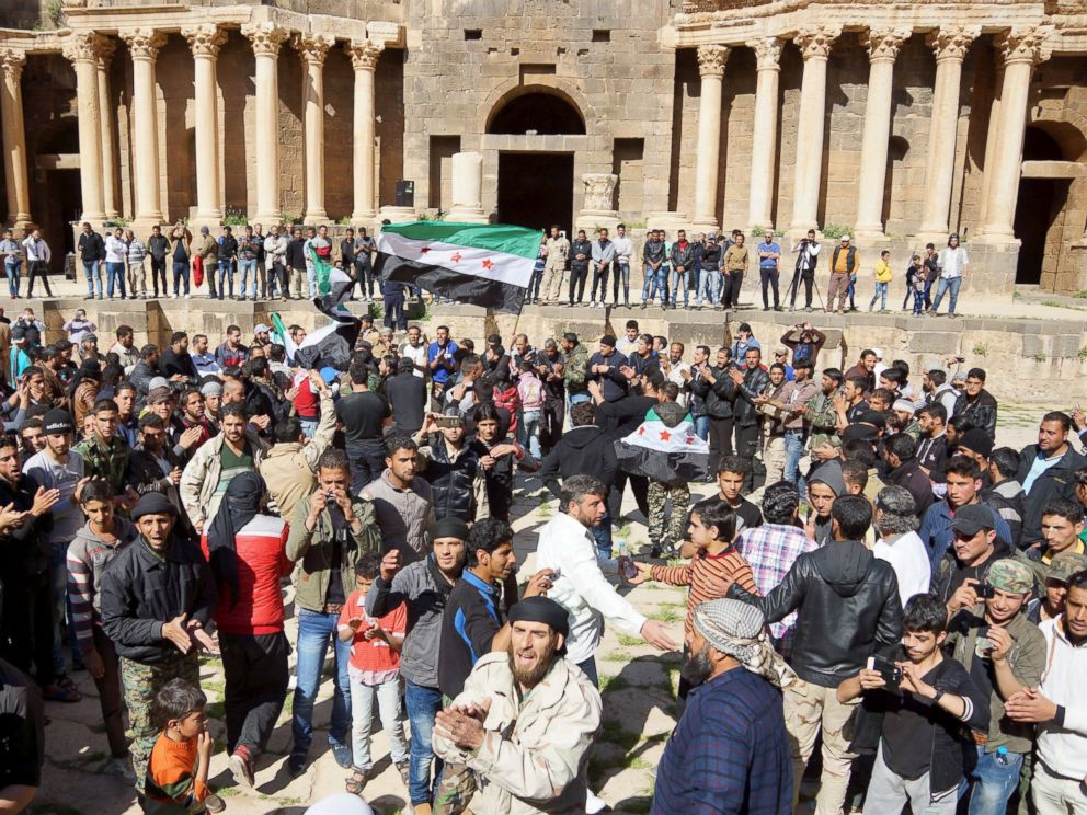 PHOTO: Protesters carry opposition flags and chant slogans during an anti-government protest inside a 2nd century Roman amphitheater in the historic Syrian southern town of Bosra al-Sham, in Deraa, Syria, March 4, 2016.